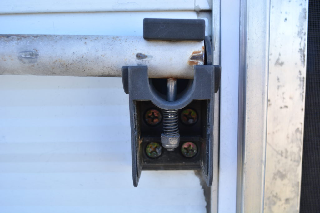 Now, using a socket or wrench, remove the nut on this spring loaded bolt. Be careful that the spring doesn't pop off and get away from you - its not under much tension, but springs will be springs. Once removed, the bolt will pull out. Repeat for the top portion of the handle, and the handle can be removed.